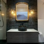 Bathroom with wall hung vanity and distressed gold framed mirror