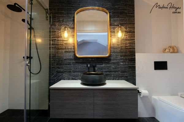 Bathroom with dark marble tiles and pendant lights hanging on either side of the wash basin