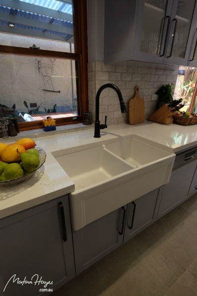 Traditional kitchen with a white farmhouse sink and a black tap