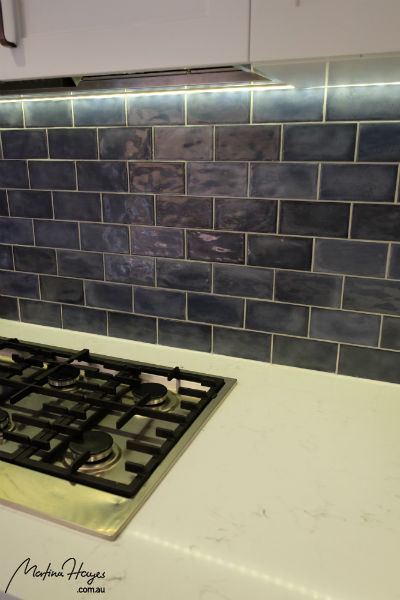 Splashback with blue subway tiles and LED strip lighting underneath the cabinet