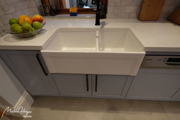 White farmhouse sink built in a duck egg blue cabinetry
