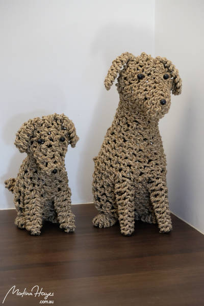 Two dogs made out of rope sitting side by side as decoration
