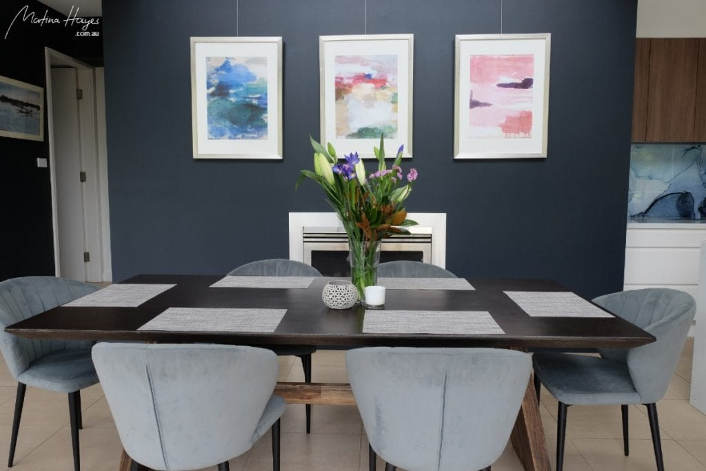 large dining space with blue velvet chairs and dark blue feature wall colour as well as being a part of a gallery wall Mosman